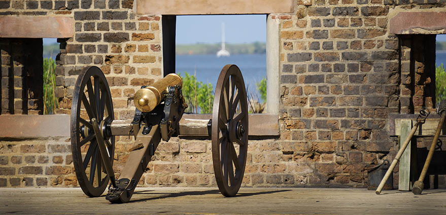 Antique cannon overlooking the ocean through a window on a brown brick wall at Fort James Jackson in Savannah, Georgia