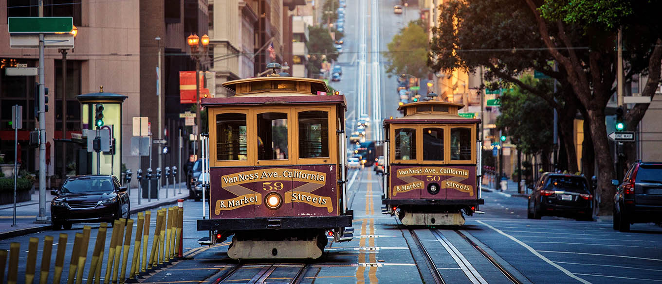 Two historic traditional cable cars travel along a San Francisco street