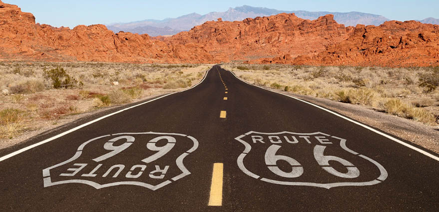 Route 66 is written on a highway with the Arizona desert and red mountains in the background against a clear blue sky