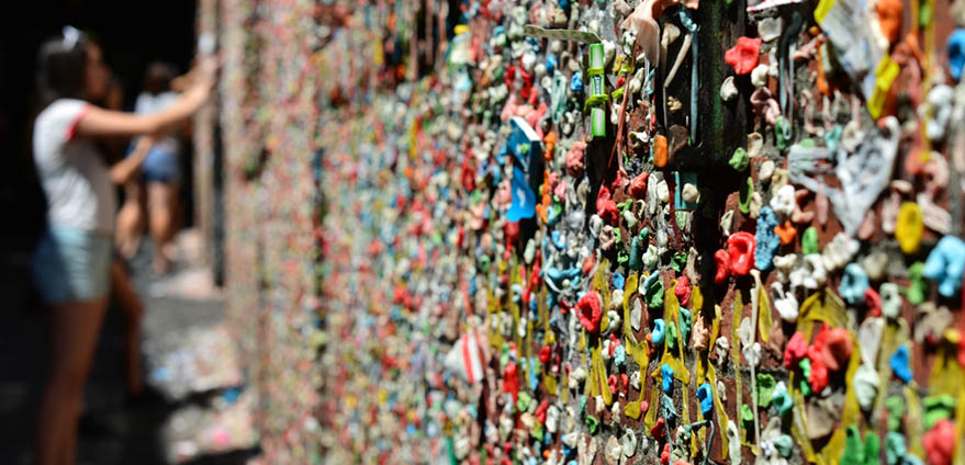 A girl adds more already-been-chewed gum to the famous Market Theatre Gum Wall in Seattle, Washington