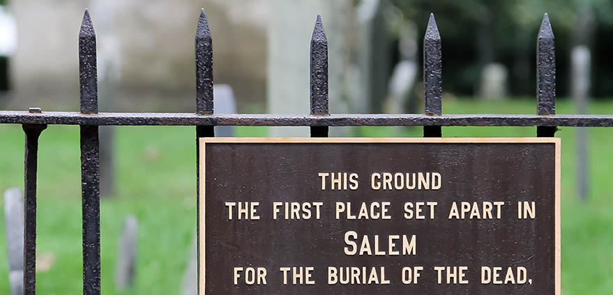 A brown sign with gold writing explaining that the area is a burial ground sits on a wrought-iron fence, with green grass, trees and the silhouette of a gravestone on it in Salem, Massachusetts