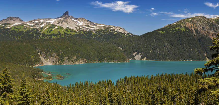 View of the turquoise Garibaldi Lake surrounded by pine trees and Black Tusk in Coast Mountains of British Columbia from a hike on the Panorama Ridge Trail in Garibaldi Proincial Park in Whistler, British Columbia