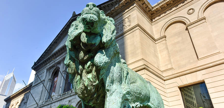 Lion statue in front of The Art Institute of Chicago on a clear, sunny day.