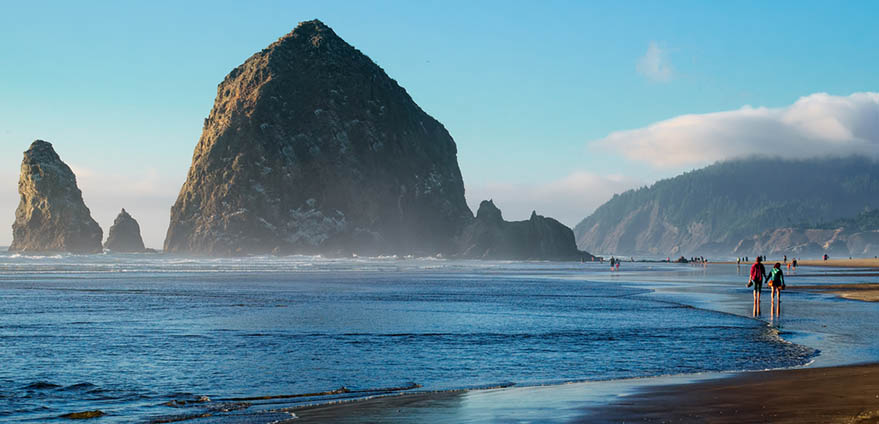 Sea stack rocks emerge from the coastal waters of Cannon Beach in Oregon