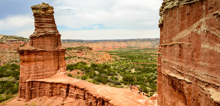 Red mountain peaks are pictured in the foreground with the Arizona desert in the background in Palo Duro Canyon State Park