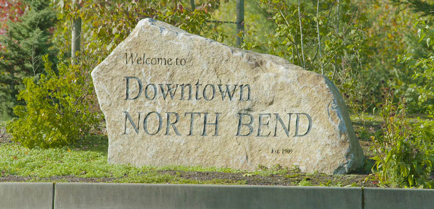 Welcome to Downtown North Bend stone signwith green trees in the background