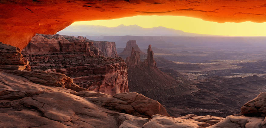 Sunrise casts a bright orange glow under Mesa Arch in Canyonlands National Park near Moab, Utah