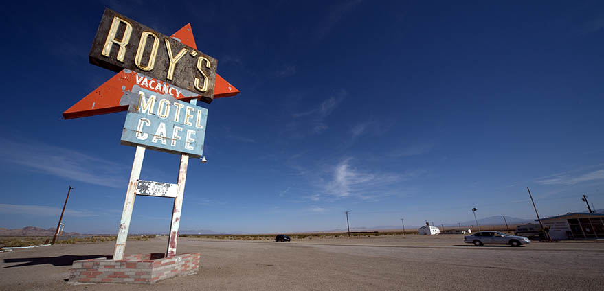 A red and blue sign reading Roy's Motel Café stands in the foreground in an empty lot with a clear blue sky in the background in Amboy, California