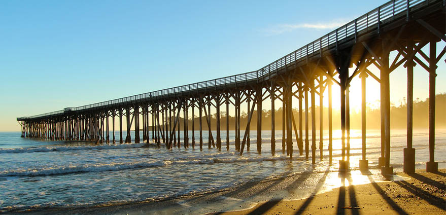 The San Simeon Pier near Hearst Castle in California casts a shadow on the beach at sunset