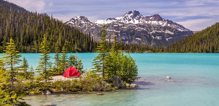 Red tent against turquoise water of Upper Joffre Lake in British Columbia, Canada