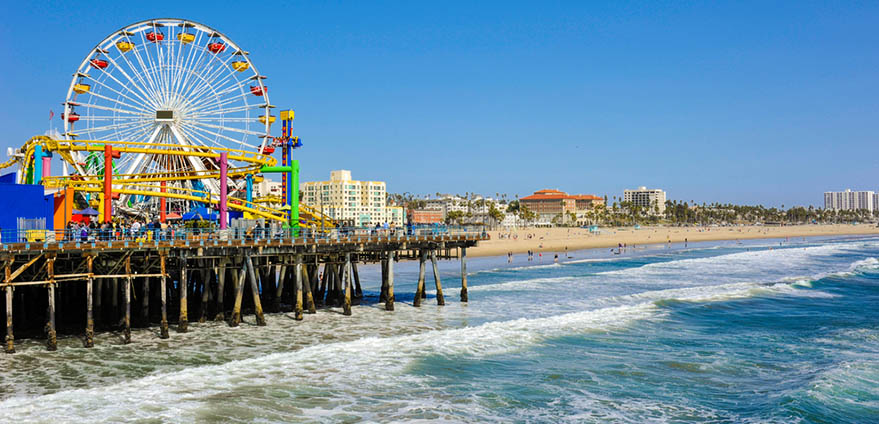 A colorful ferris wheel and rollercoaster are pictured in the foreground to the left on top of a pier, with water crashing below and a clear blue sky in the background at Santa Monica Pier in California