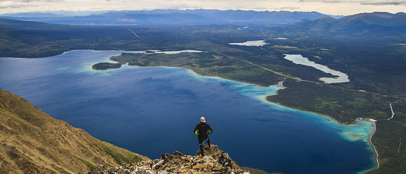 Hiker enjoying the view above the Kathleen lake in Kluane National Park, Yukon