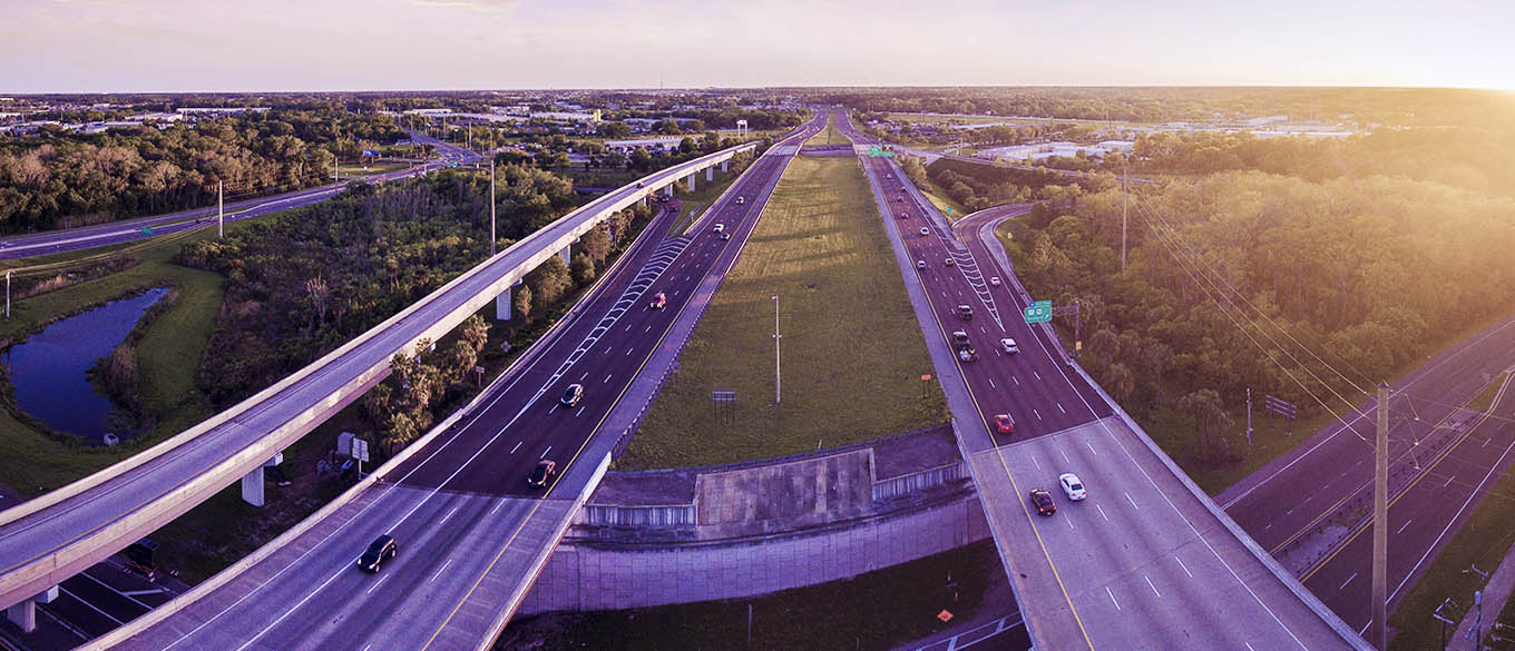 Aerial view of Interstate 4 in Sanford, Florida, a haunted highway on a clear day with sunburst on the side and lush greenery around the highway