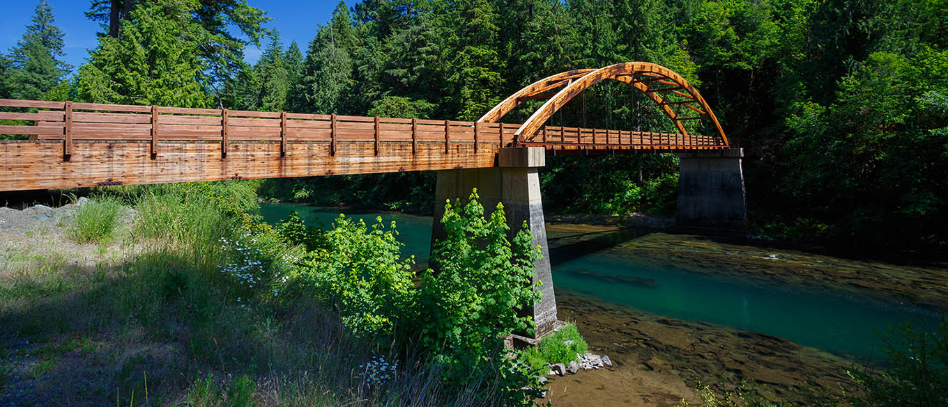 The wooden Tioga Bridge stretches over the turquoise waters of the North Umpqua River in Oregon