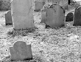 A black and white photo of old, cracked gravestones in grass in Salem, Massachusetts