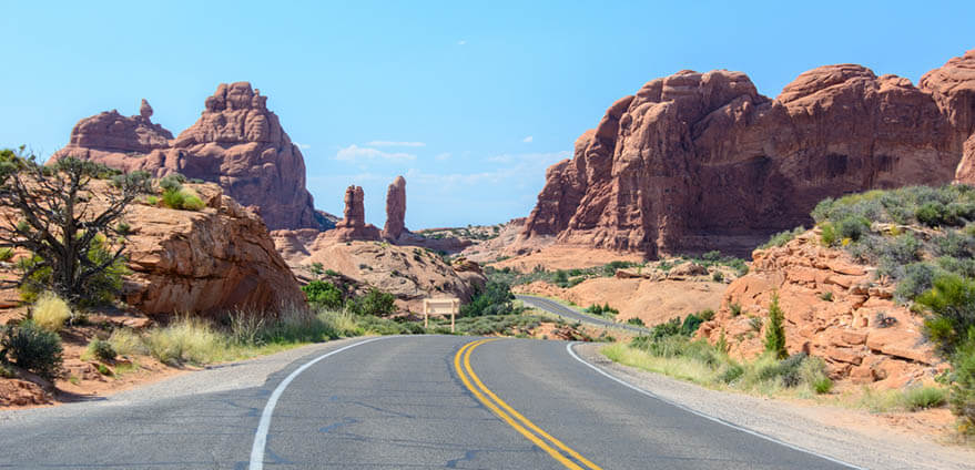 A blue afternoon sky shines over a winding road in Arches National Park, Moab, Utah.