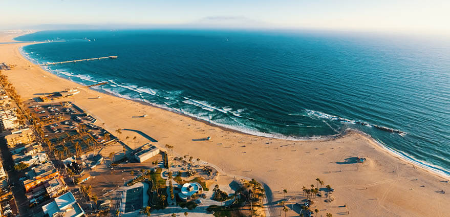 Aerial view of the shoreline in Venice Beach, CA on a bright summer day.