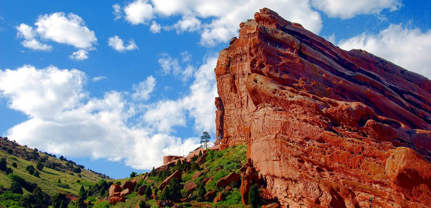 One of the large red rock formations at Red Rocks Park, home to the famous Red Rocks Ampitheater in Morrison, Colorado with blue sky and white puffy clouds in the background