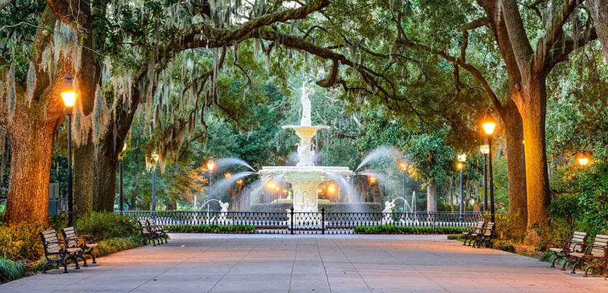 A regal fountain in Forsyth Park amongst grand oak trees dripping in Spanish Moss in Georgia at dusk