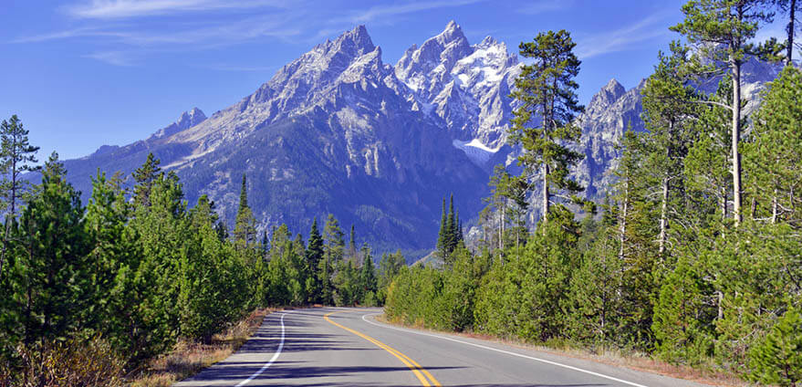 A view of the snow-capped mountains in Wyoming from the road approaching Grand Teton National Parks on a sunny morning.