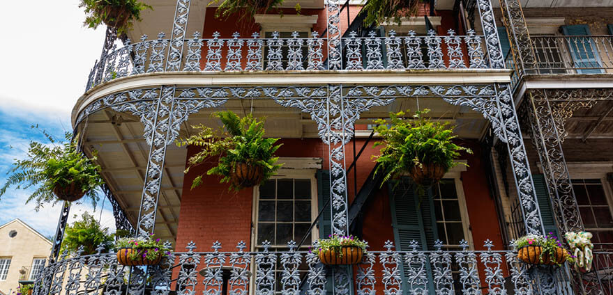 Colorful architecture in the French Quarter sit beneath a bright afternoon sky in New Orleans, Louisiana.