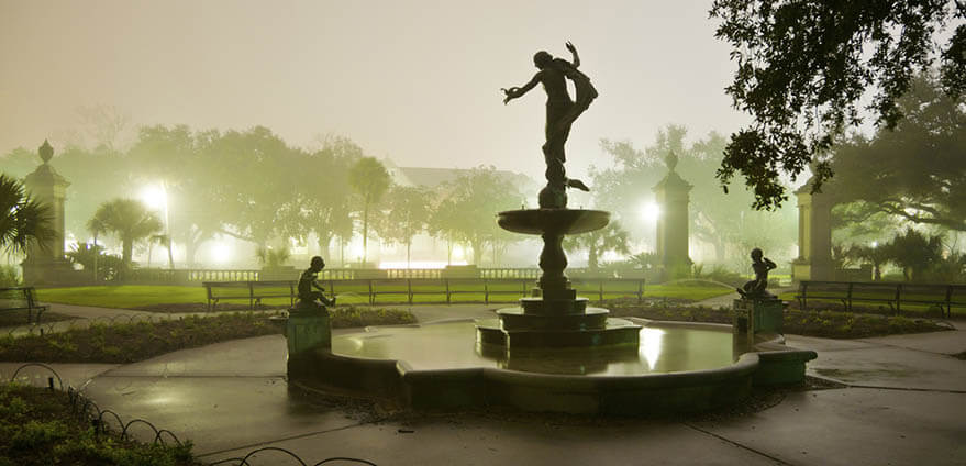 A silhouette of a statue and fountain are seen at twilight in Audubon Park, New Orleans, Louisiana.