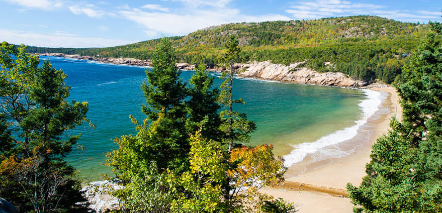 View of sand beach in Acadia National Park in Maine on an Autumn day, surrounded by forest and mountains along the coast of the Atlantic Ocean.