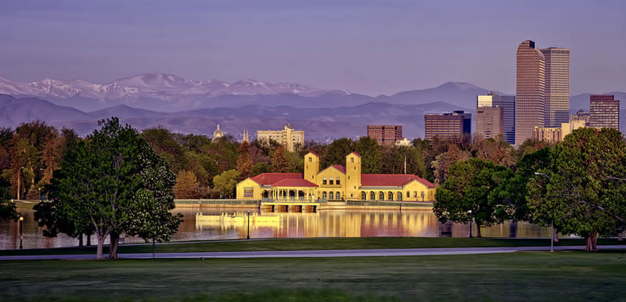 The Denver Museum of Science and Nature, a white building with red roof sitting on a lake, illuminated at sunrise with a view of the mountains and the Denver skyline in the background