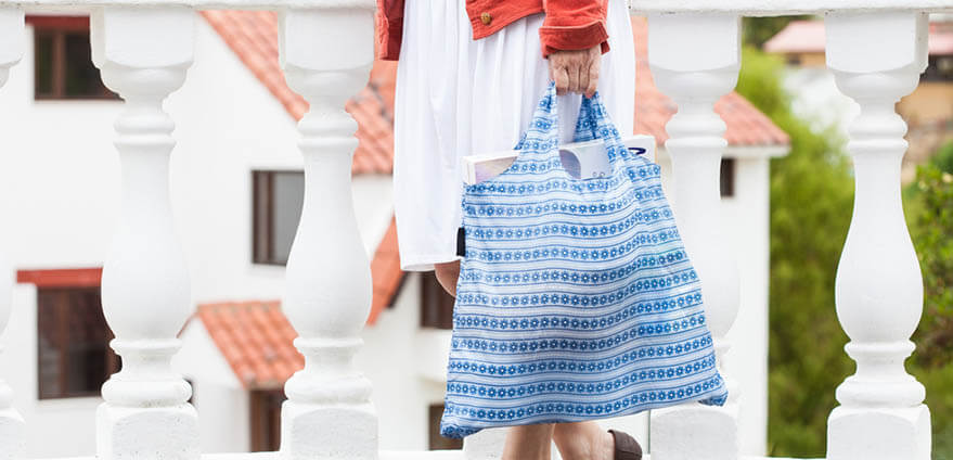 Eco-conscious woman wearing a red jacket and white dress with brown heels carrying groceries in a white and blue striped reusable shopping bag.