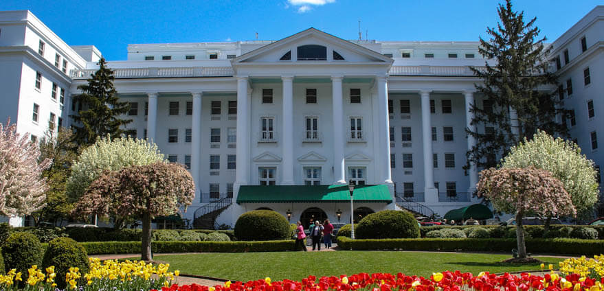 Visitors stand in front of the grand front entrance to The Greenbrier in West Virginia on a summer afternoon