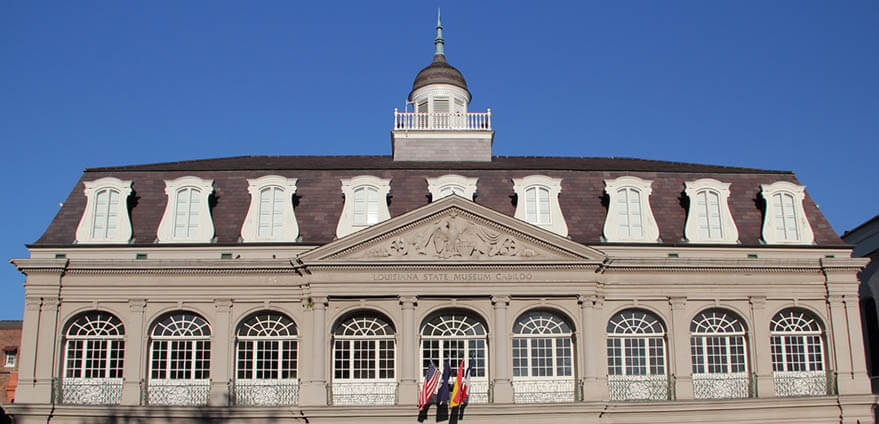 A historic colonial building in the French Quarter of New Orleans, Louisiana sits beneath a blue morning sky.