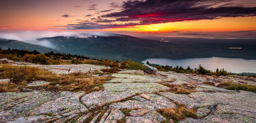 A gorgeous view of a sun rise in Acadia National Park in Maine at Cadillac Mountain with an orange, pink, red and purple sky in the background and a rocky ledge in the foreground