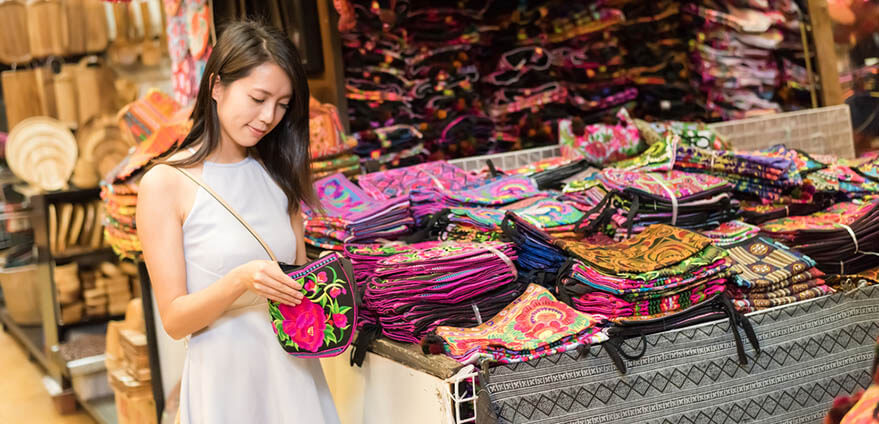 Young Asian woman traveling and shopping locally at Chatuchak weekend market, Bangkok, Thailand.