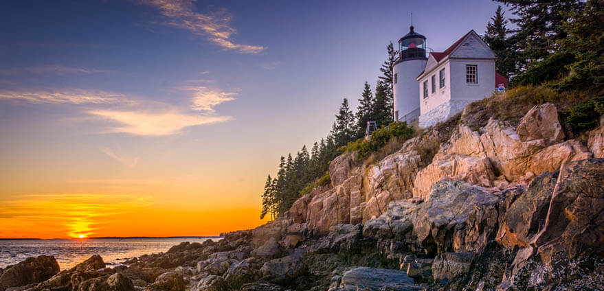 The Bass Harbor Lighthouse – a white lighthouse with red and black trim on the rocky coast of the Atlantic Ocean - is stunning at sunset in Acadia National Park, Maine.