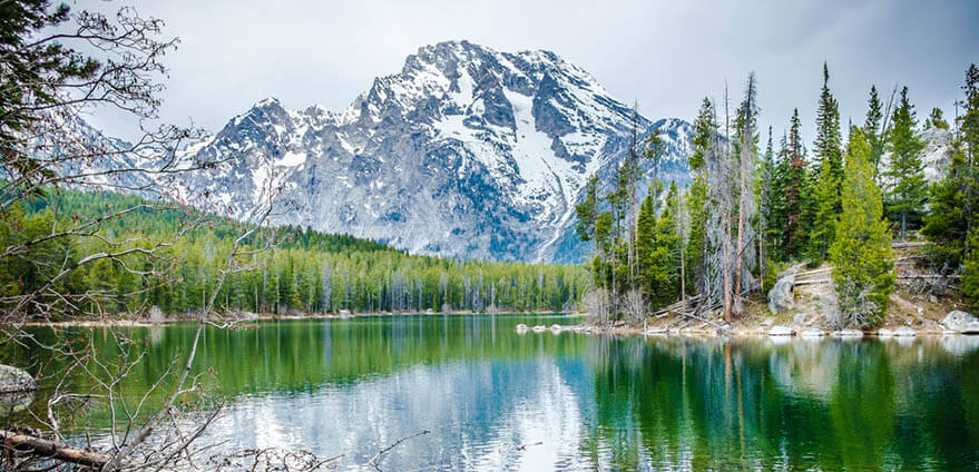 Leigh Lake in Grand Teton National Park is seen reflecting the snow-covered mountains on a misty morning.