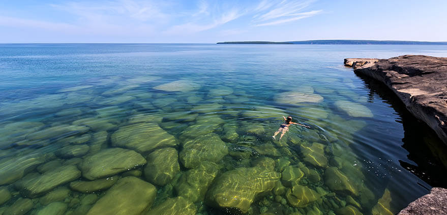 Girl swims in the clear water of Lake Superior in the Upper Peninsula of Michigan on clear day, showing rocks below and cliffs above