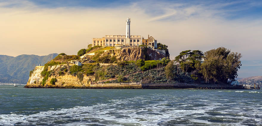 Alcatraz Island in San Francisco is hit by the bright sun on a partly cloudy afternoon.