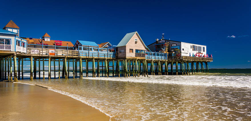 Colorful buildings atop the Atlantic Ocean Pier in Old Orchard Beach in Maine against a blue sky