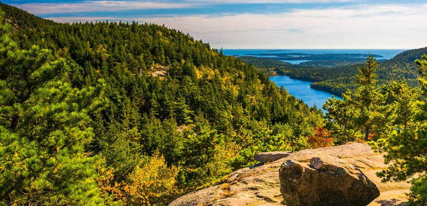 View from North Bubble, in Acadia National Park, Maine on sunny day shows a landscape of trees and cliffs with rivers and the Atlantic ocean in the far background