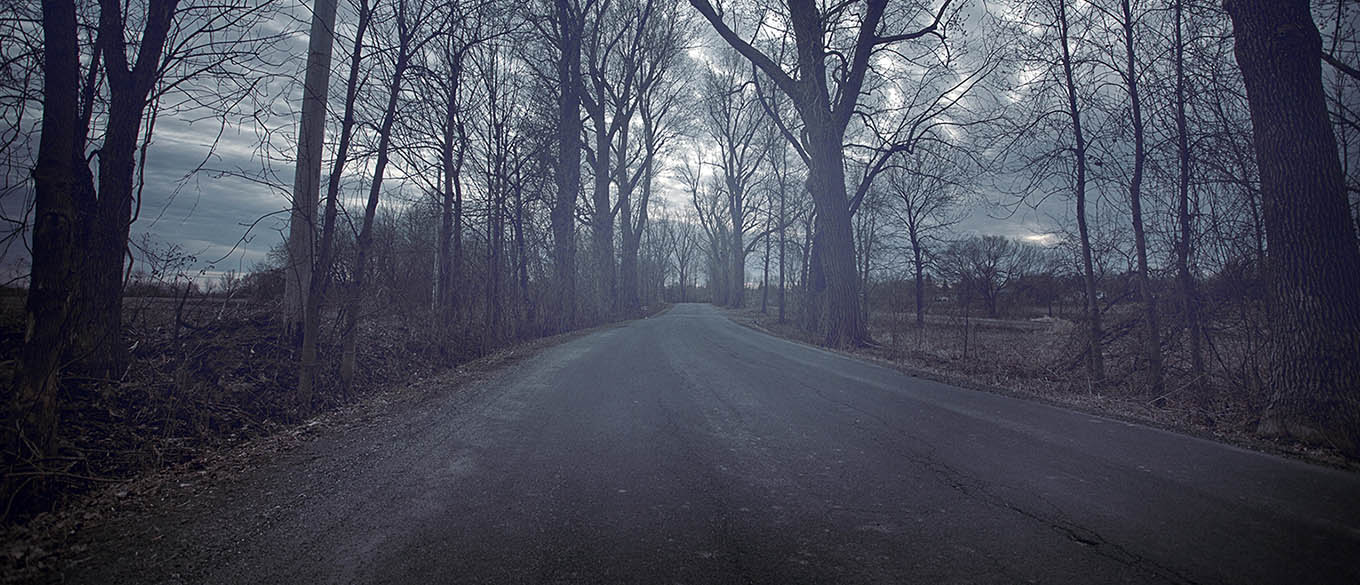 A haunted, gloomy road waits to be explored on a cold and dark afternoon.