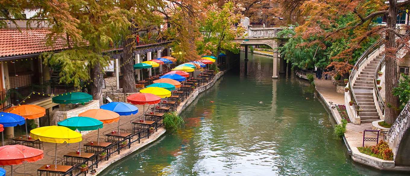 A view of the River Walk with colorful umbrellas in San Antonio Texas on clear day.