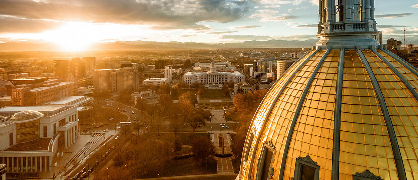 A view of the city of Denver drenched in golden sun from the roof of Colorado State Capital building at sunset shows the top spire of the Capital building in the foreground
