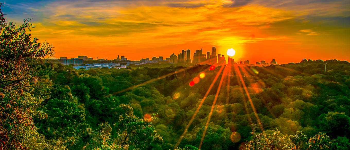 A view of the Austin city skyline from a hiking trail at sunrise.