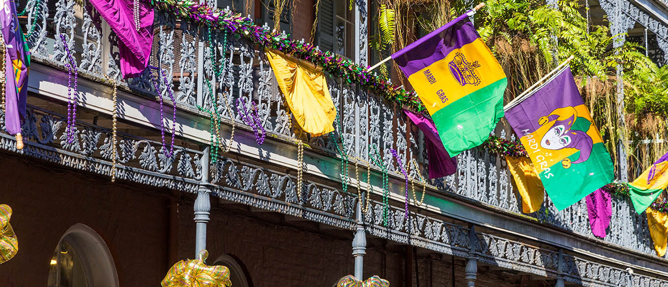 Ironwork galleries on the Streets of French Quarter decorated for Mardi Gras in New Orleans, Louisiana are hit by the hot afternoon sunlight