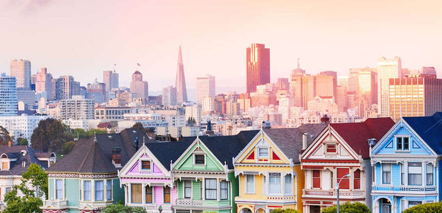 The white Victorian- style homes of the Painted Ladies are pictured in the daytime with the skyline of San Francisco, California in the background