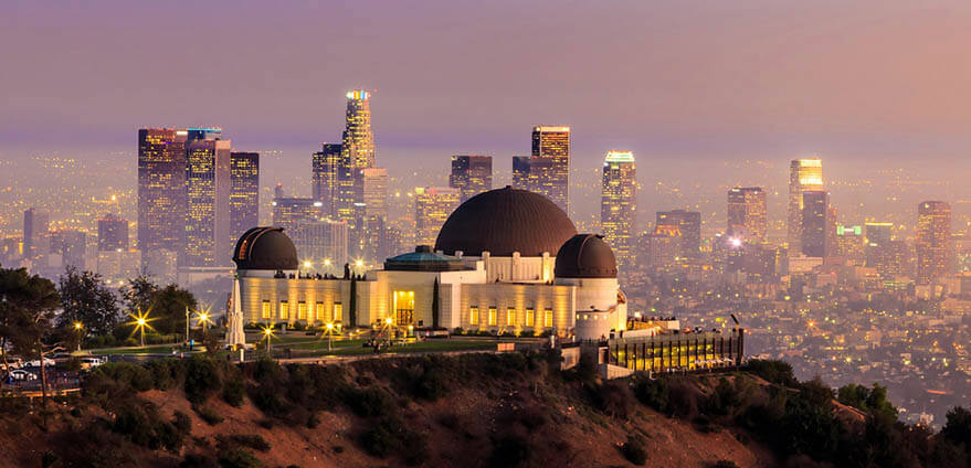 View of Griffith Observatory in Los Angeles, California at dusk with the downtown Los Angeles skyline in the background