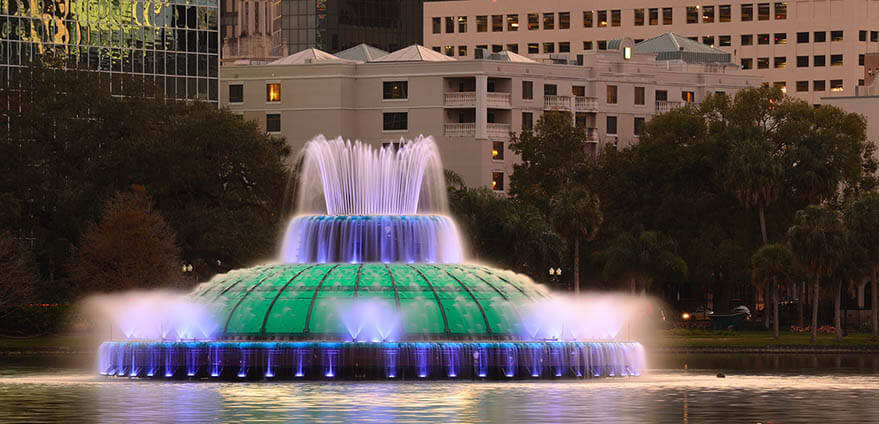 Colorful lights illuminate a fountain at night in Eola Lake in Orlando, Florida