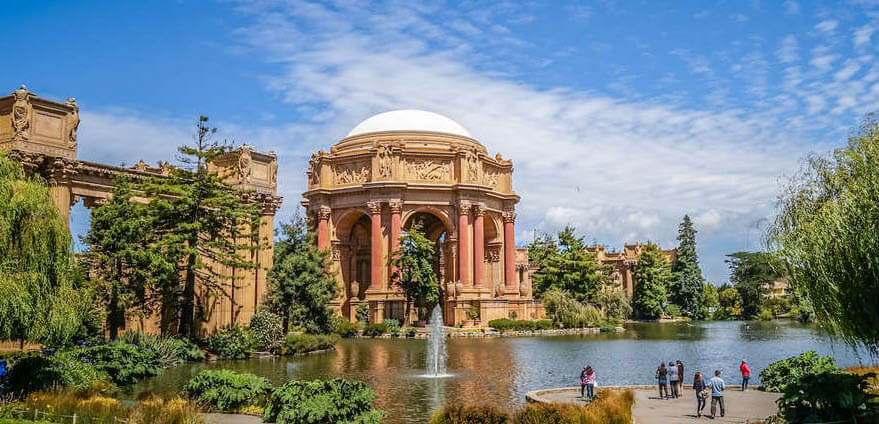 The roman style architecture of The Presidio of San Francisco are pictured with light brown, roman style columns and buildings in front of a body of water and a clear blue sky in the background in San Francisco, California