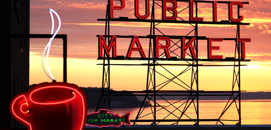 Ndeon Pike Place Market signage at dusk with water in the background