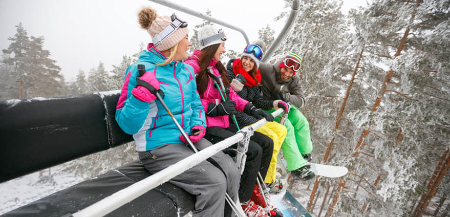 Four friends sitting on a chair lift on a snowy spring day in colorful ski and snowboard gear.